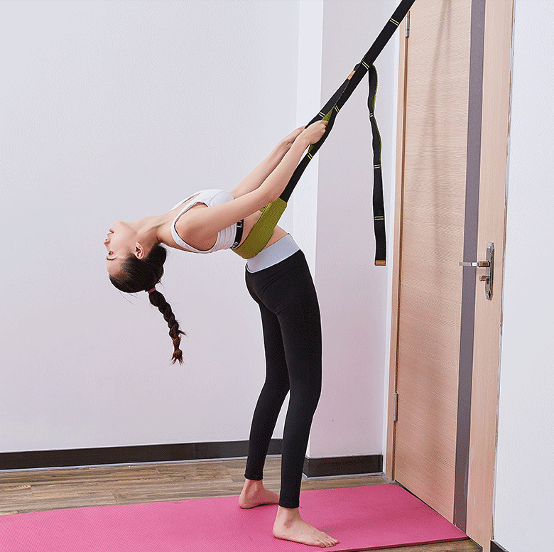 woman is doing pilates using her yoga belt on her pink mat
