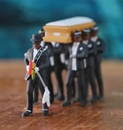 Black man carrying coffin toy